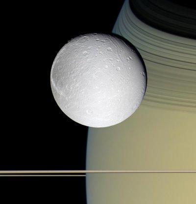 Dione vista con Saturno y sus delgados anillos. Crédito: Cassini/NASA.