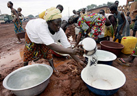 Women fill buckets with water at a water point in a northern neighbourhood of Korhogo, 14 September 2005, where drought has hit the region for the past two months.