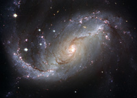 The barred spiral galaxy NGC 1672, showing up clusters of hot young blue stars along its spiral arms, and clouds of hydrogen gas glowing in red. Delicate curtains of dust partially obscure and redden the light of the stars behind them. NGC 1672's symmetric look is emphasised by the four principal arms, edged by eye-catching dust lanes that extend out from the centre.
