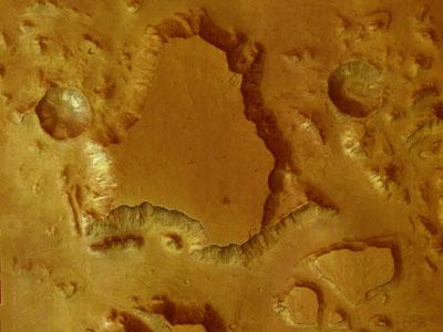 Une belle vue du coeur du grand canyon martien. Le plateau visible au centre est situé à une altitude de 3 km et le grand cratère a un diamètre de 7,6 km.