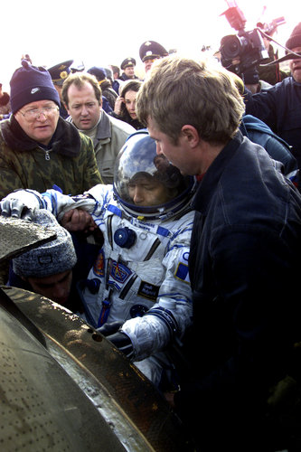 Claudie is helped out of the Soyuz