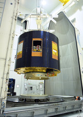 The two payload fairing half-shells are moved into position
