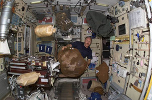 Astronaut Bowersox moves bagged items on ISS