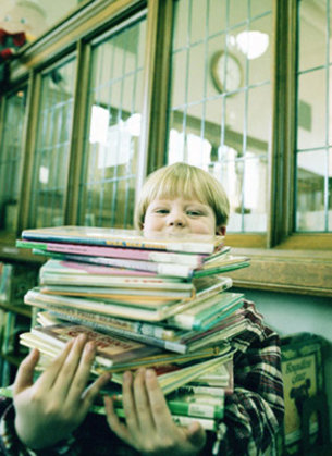 Boy holding a stack of picture books