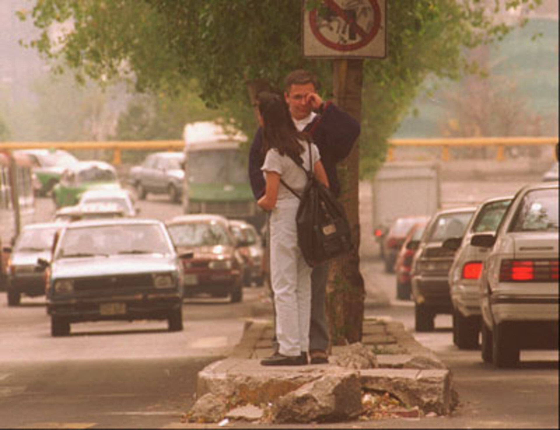 At a Mexico City intersection, an unidentified man rubs his eyes as the couple waits to cross the traffic