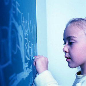Elementary school girl writing on chalk board