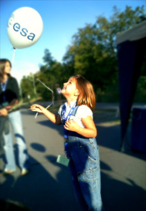 A young visitor releases a mock weather balloon