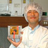 A student holds one of the smaller CubeSats