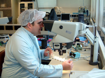Neil Melville, project manager for SSETI Express, checking the power interface node soldering as it is delivered to ESTEC