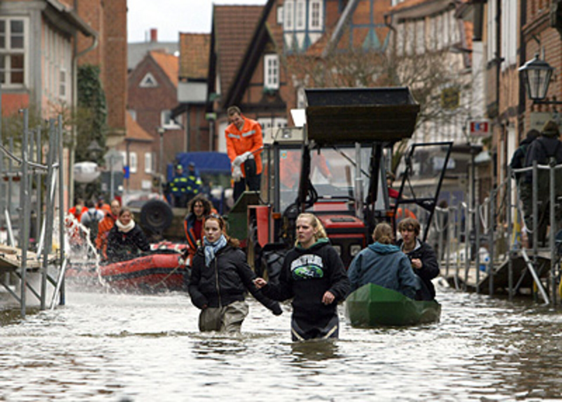 Residents make their way through a flooded street
