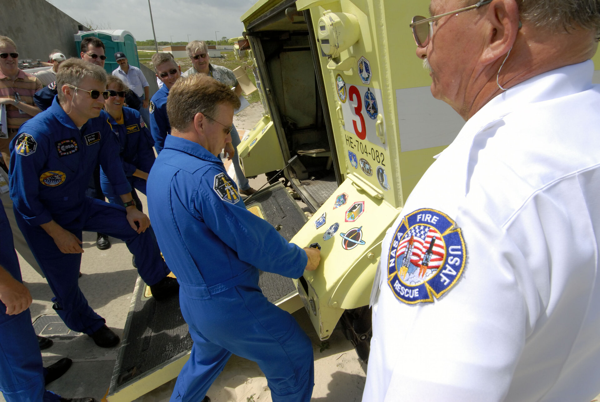 Commander Steven Lindsey applies a mission sticker to a fire rescue vehicle at NASA's Kennedy Space Center