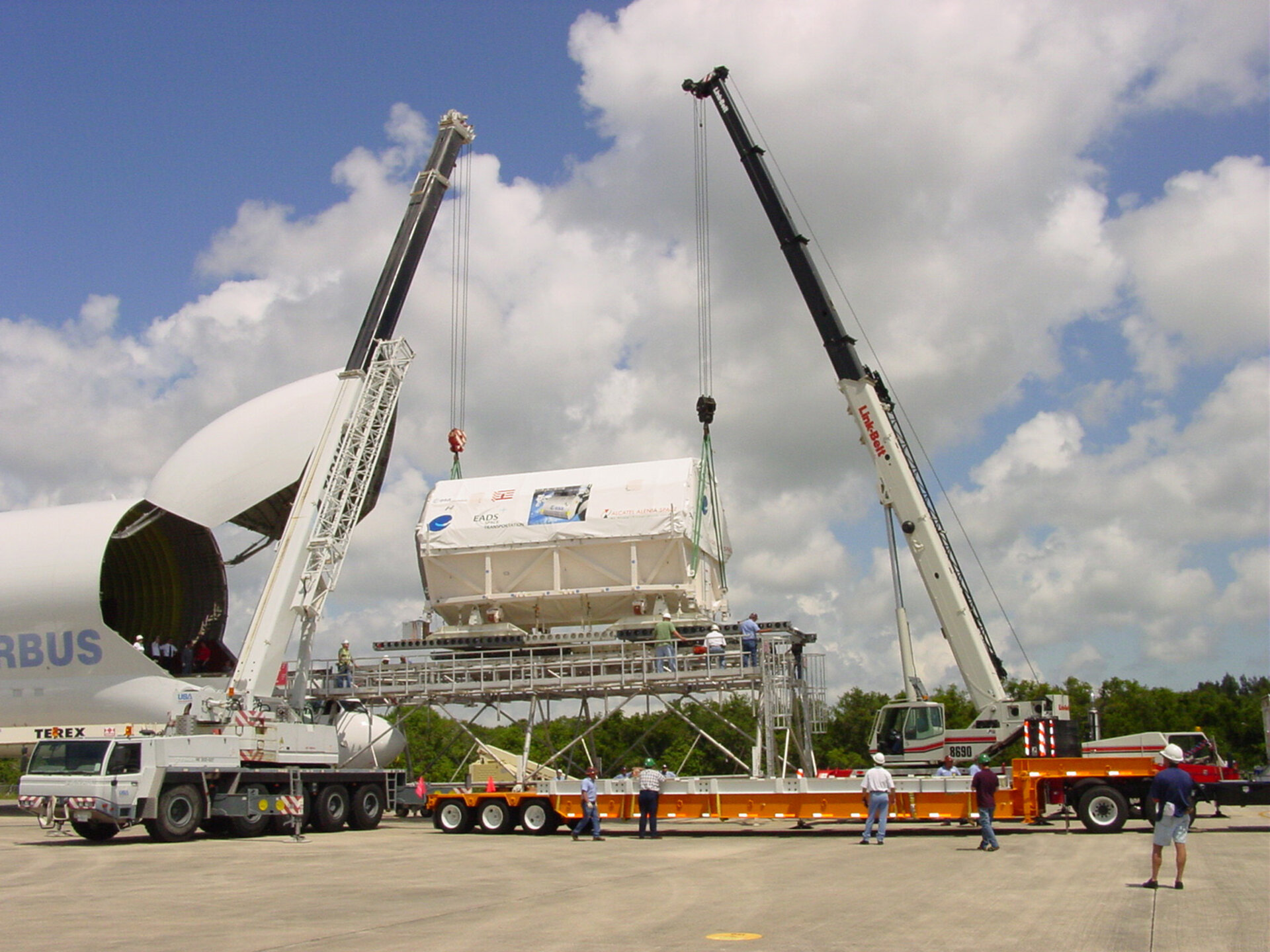 Two cranes lower the Columbus laboratory toward a flatbed truck