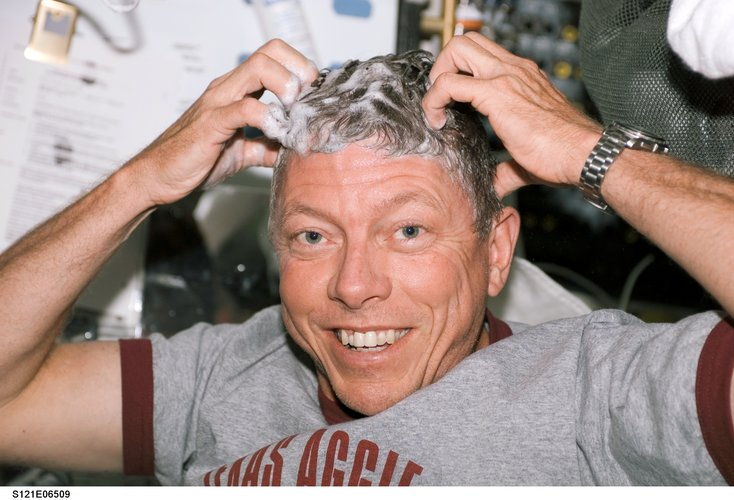Astronaut Michael E. Fossum washes his hair on the middeck of the Space Shuttle Discovery