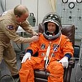 Thomas Reiter is helped with his launch suit