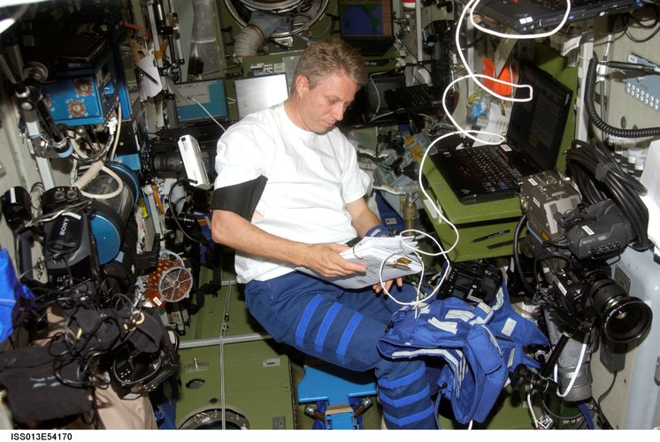 Thomas Reiter looks over a procedures checklist in the ISS Zvezda Service Module