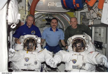 Expedition 13 with two American spacesuits in the Quest Airlock