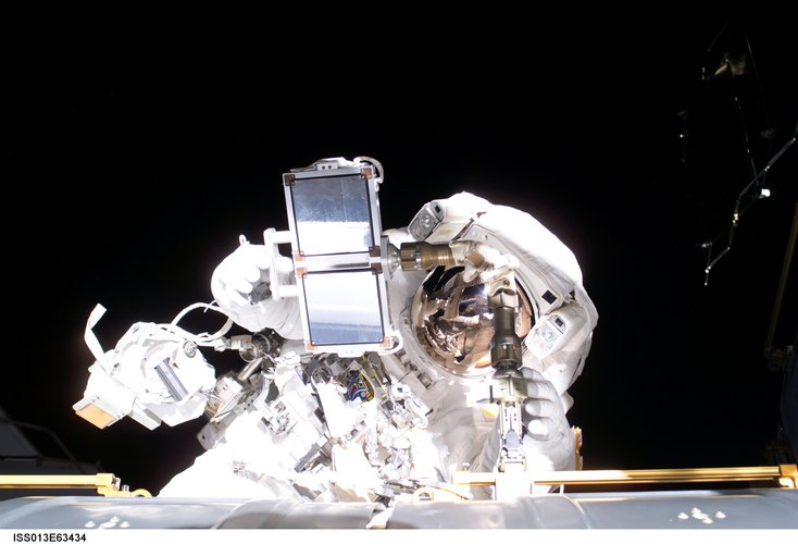 Thomas Reiter carries equipment for one final planned tasks during the spacewalk on 3 August 2006