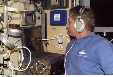 Thomas Reiter wears a communication system headset while using a computer in the Zvezda