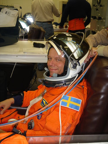 Christer Fuglesang is helped into his orange Advanced Crew Escape Suit (ACES) in preparation for the practice countdown