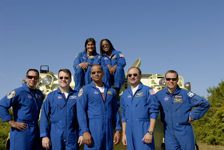 STS-116 mission crewmembers pose next an emergency evacuation vehicle
