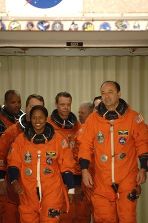STS-116 Shuttle crew, wearing their orange Advanced Crew Escape Suits (ACES), walkout for the practice countdown at KSC