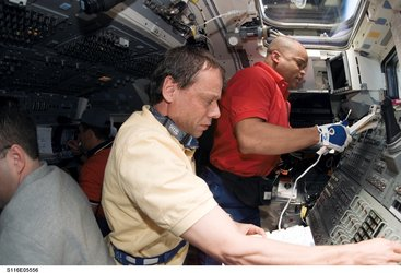 Christer Fuglesang and Robert Curbeam at work on board the Space Shuttle