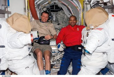 Christer Fuglesang and Robert Curbeam inside the Quest airlock with the American EVA suits