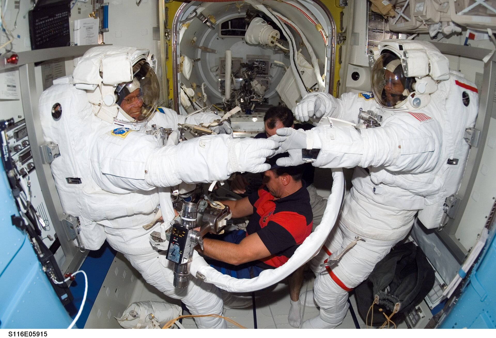 Christer Fuglesang and Robert Curbeam prepare for the first spacewalk