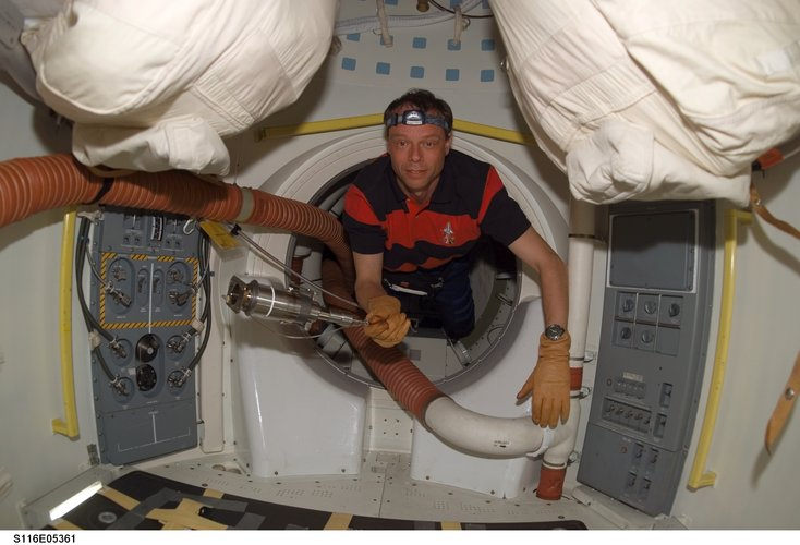 Christer Fuglesang holds a tool as he floats through a hatch on Space Shuttle Discovery