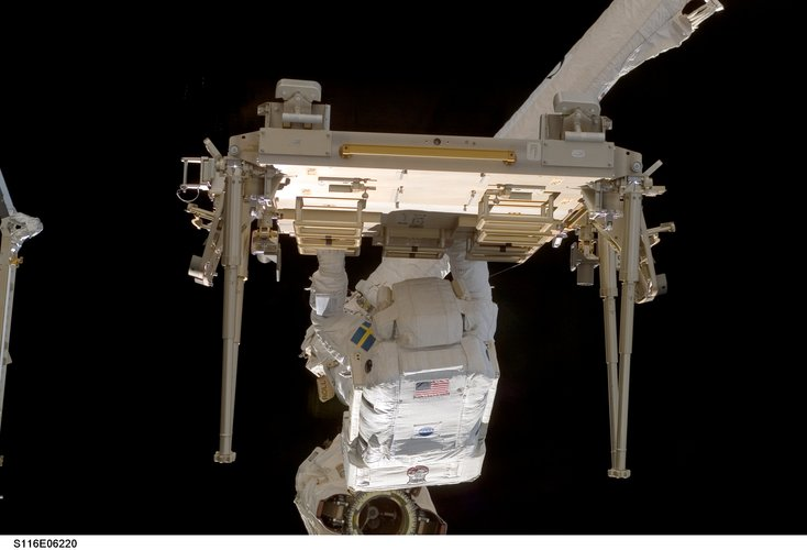 Fuglesang stands on a platform at the end of the Station's robotic arm