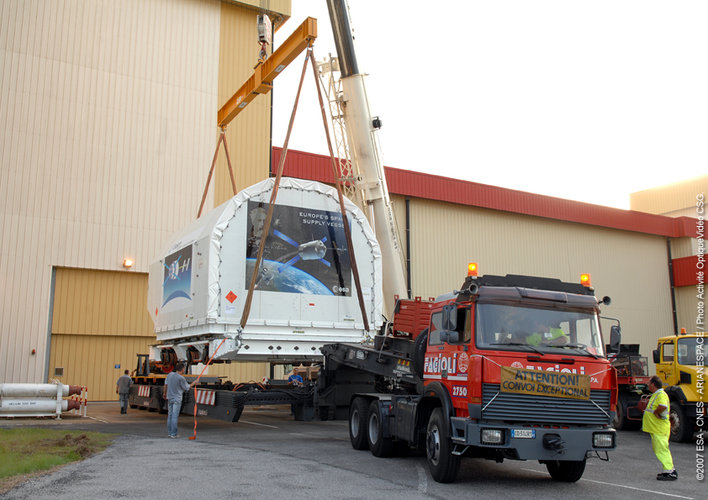 Container holding the ATV Integrated Cargo Carrier is lifted off the back of a truck at Europe's Spaceport in Kourou