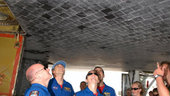 Members of the STS-118 crew take a look at the damaged tile