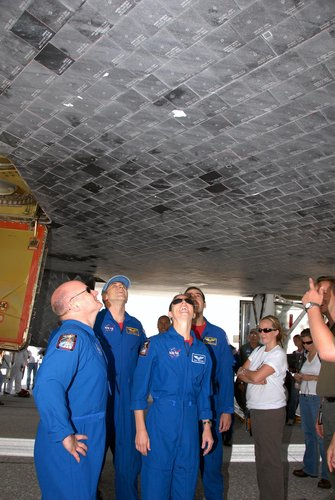 Members of the STS-118 crew take a close look at the damaged tile on the underside of Endeavour