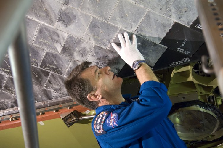 Paolo Nespoli inspects Discovery's heat resistant tiles during CEIT at Kennedy Space Center
