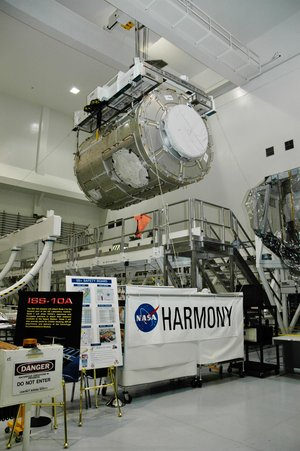 An overhead crane lifts the U.S. Node 2 module, known as Harmony, from its stand.