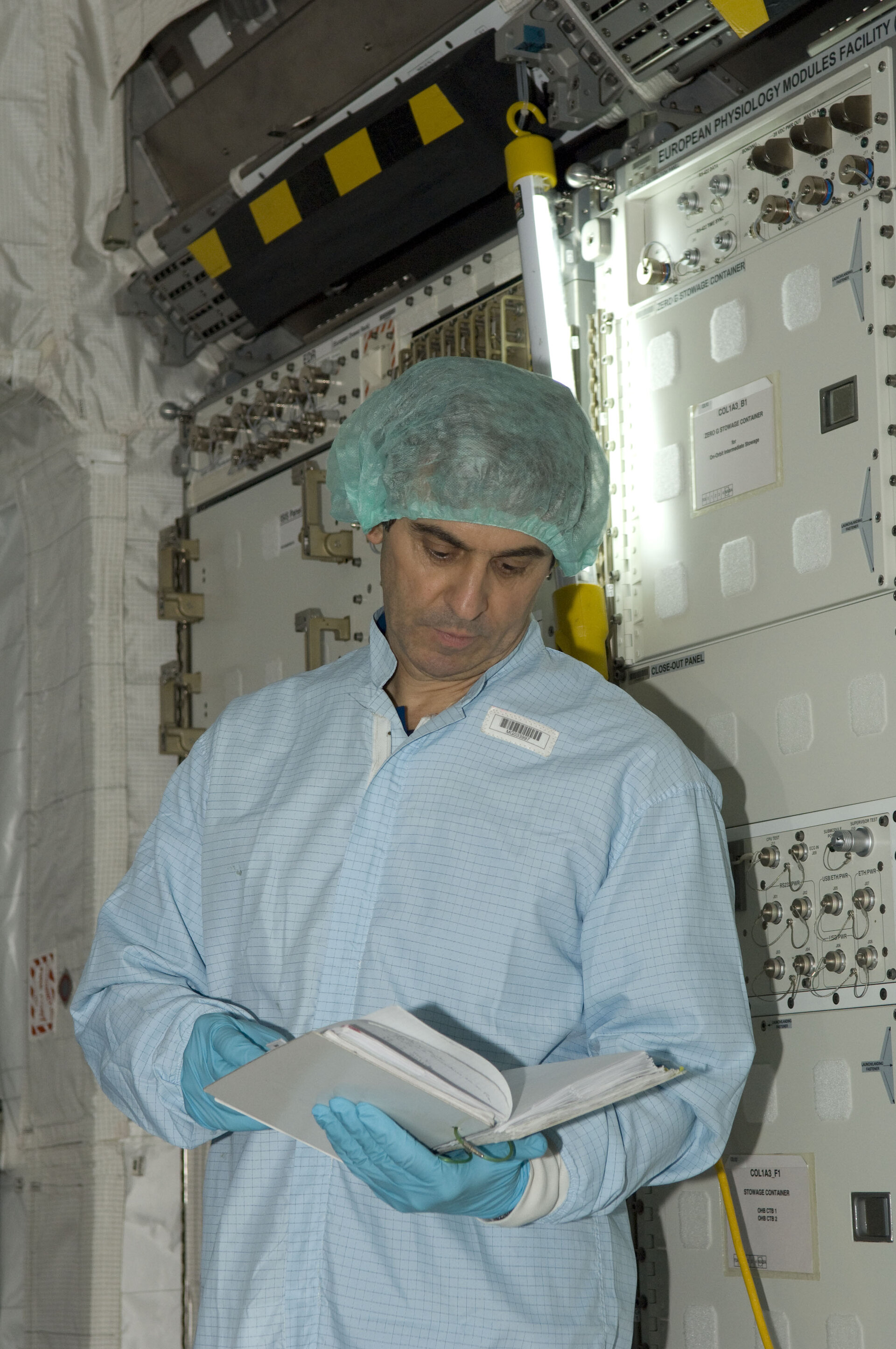 ESA astronaut Leopold Eyharts consults documentation during an inspection of interior European Columbus laboratory