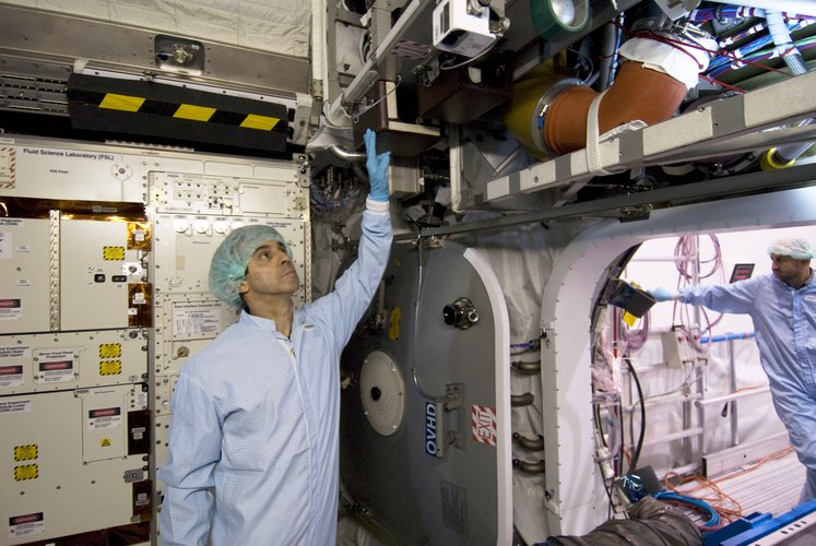 ESA astronaut Leopold Eyharts inspects the interior of the European Columbus laboratory