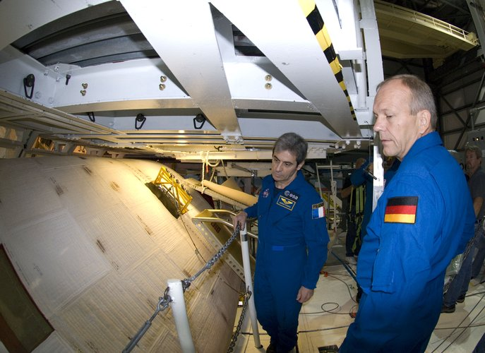ESA astronauts Leopold Eyharts and Hans Schlegel during an inspection of Space Shuttle Atlantis