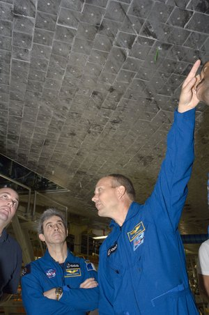 ESA astronauts Leopold Eyharts and Hans Schlegel during inspection of Space Shuttle Atlantis at KSC, Florida