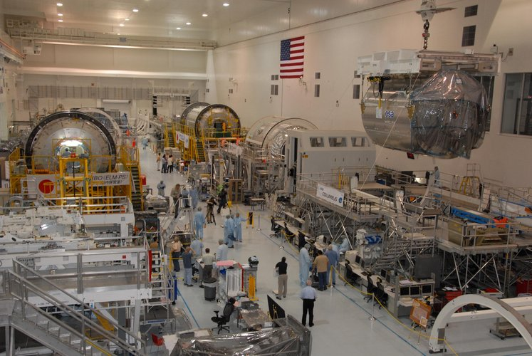 An overhead crane lifts the European Columbus laboratory module away from its stand