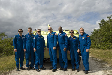 STS-122 crew pose next to an emergency evacuation vehicle at Kennedy Space Center, Florida