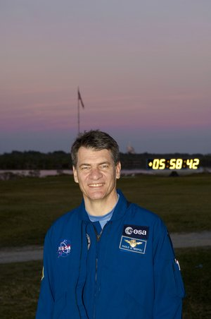 Paolo Nespoli stands in front of the launch countdown clock at KSC