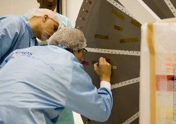 Project team members write messages on the Integrated Cargo Carrier cover