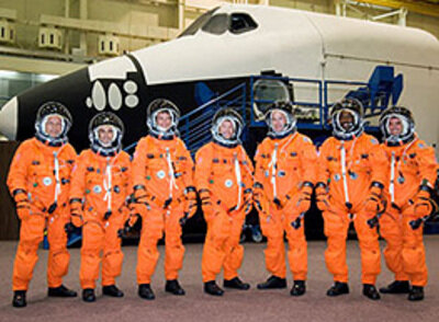 Left: STS-122 crew members, including  the European Space Agency (ESA) astronauts Hans Schlegel and Léopold Eyharts. Right: STS-122 Mission patch