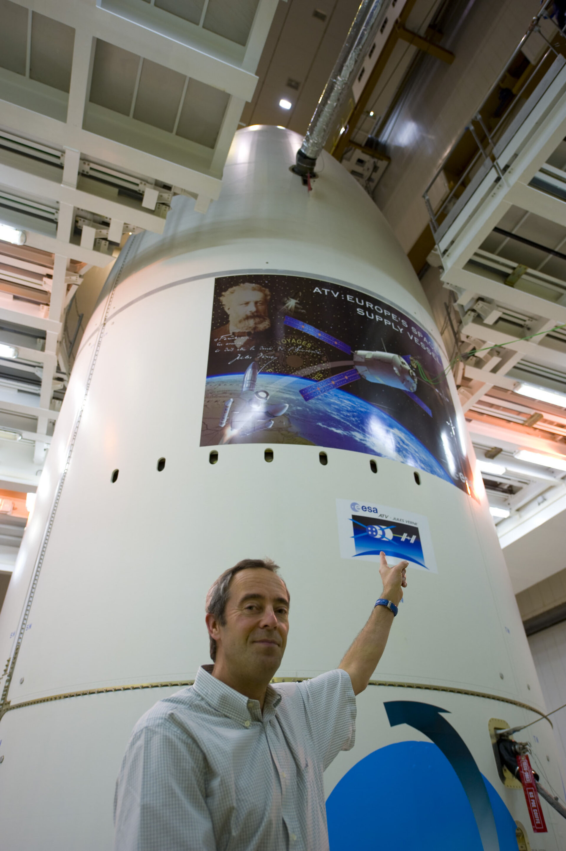 Jean-François Clervoy points to stickers on the Ariane 5 ES-ATV launcher fairing