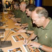 Signing autographs after presentation of mission