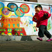 A young Chinese girl plays outside her home