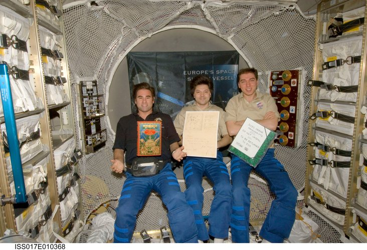 ISS Expedition crew displays the Jules Verne book and manuscripts
