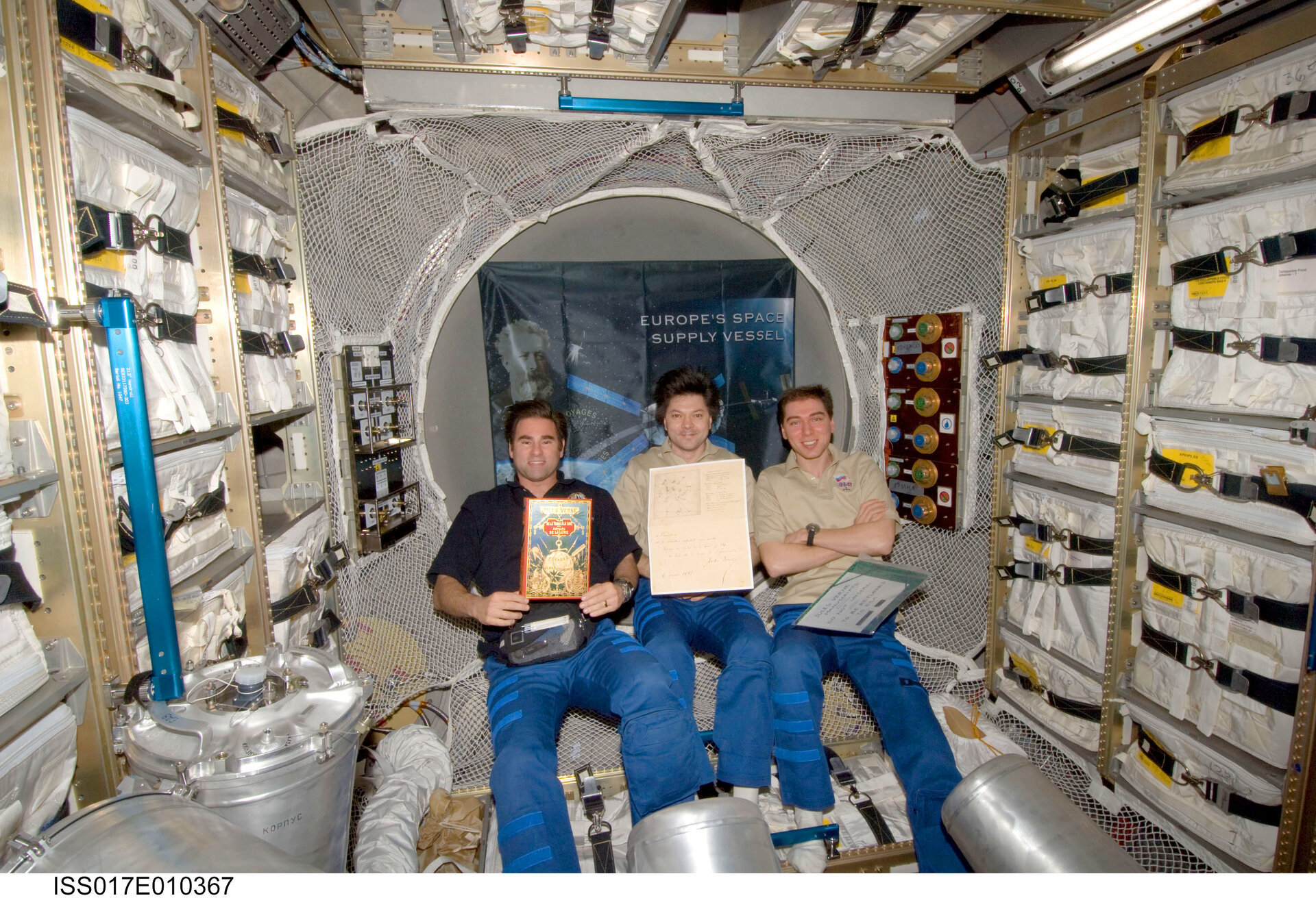 ISS Expedition crewmembers display the Jules Verne book and manuscripts delivered to the ISS