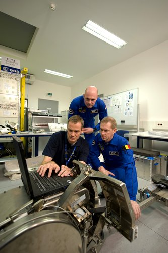 Frank De Winne and Andre Kuipers receive instruction in use of the Flywheel Exercise Device